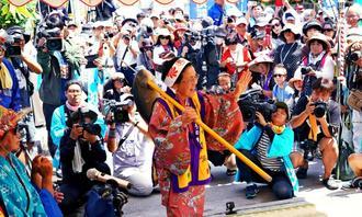 神事のトゥダヌイュー。モリで突き刺した魚を担ぎ、舞を披露する神人=8日、うるま市・平安座島(下地広也撮影)