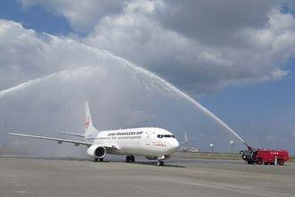 就航を歓迎する放水を受け到着したJTAの新機材ボーイング737-800型機=10日午後、宮古空港