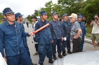 県道70号を通行止めにした警察官に抗議する市民=10日午前9時半すぎ、東村高江
