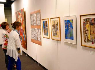 「第13回NORI絵画13人展」の作品に見入る来場者=15日、那覇市久茂地・タイムスギャラリー
