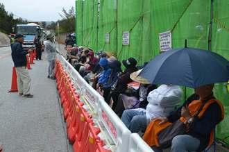 小雨が降る中で座り込みをする人々=18日午前9時半ごろ、名護市辺野古の米軍キャンプ・シュワブゲート前