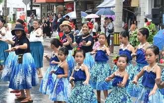 雨の中、沿道の声援を受けながらフラを披露するパレードの参加者=15日、宮古島市・下里大通り(渡辺奈々撮影)