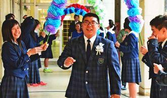 クラスメートが作った花道をくぐる比嘉力さん=12日、名護市・大宮中学校