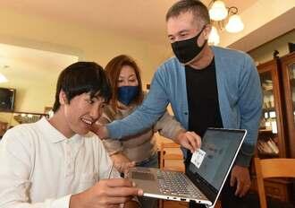 ホームページで受験番号を確認し、両親と合格を喜ぶ仲村伊織さん(左)=10日午前9時15分、北中城村島袋