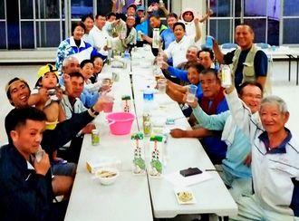 宮里優作選手のツアー4勝を祝い、乾杯する東村平良の区民ら=30日夜、同区公民館(池原太区長提供)