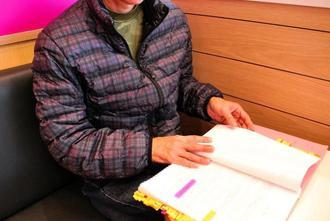 裁判関連の資料を手にする金城忠司さん。沖縄労働局の調査で従業員だと認められ、最近やっと、失業給付金の受給がスタートした