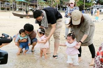 海開きされた鹿児島県・奄美大島の浜辺で、女児の足を海水につける保護者ら=14日午前