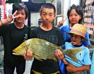 西崎海岸で64・5センチ、3・2キロのタマンを釣った赤嶺優樹さん(左から2人目)=5月27日
