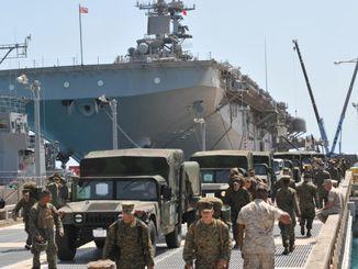 東日本大震災の被災地支援を終え、強襲揚陸艦エセックス(後方)から降り立つ米海兵隊員=2011年4月12日、うるま市・ホワイトビーチ