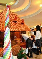 大きなお菓子の家に見入る八重山商工高生=石垣市真栄里、ANAインターコンチネンタル石垣リゾート