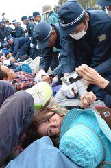 工事車両が基地内に入るのを防ごうと出入り口で座り込み、機動隊員に強制排除される女性。悲しげな瞳でカメラを見つめた/11月28日朝、沖縄県名護市辺野古