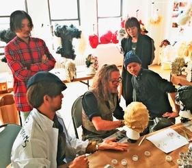 ヘアスタイリストのジュリアン・ディスさん(前列中央)と特別展を準備する(前列左から時計回りに)新垣立裕さん、伊波信秀さん、比嘉亮至さん、村吉良さん=4月下旬、米ニューヨーク・コムデギャルソンの倉庫