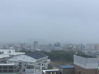 大雨で沖縄タイムスからは那覇新港が見えず、かすかにクルーズ船が見える=19日午後1時ごろ、那覇市