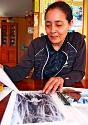 父の幼少期の写真を見て懐かしむ森根かおりさん=6日、沖縄市古謝