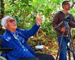 電動車いすで移動する大重潤一郎さん(左)と、助監督の比嘉真人さん=5日、久高島