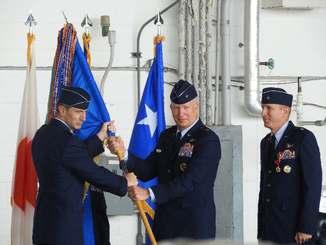 在日米軍のケビン・シュナイダー司令官(左)から第18航空団の旗を受け取った第18航空団新司令官のジョエル・キャリー氏(中央)。右は前司令官のケース・カニングハム氏=8日午前、嘉手納基地内