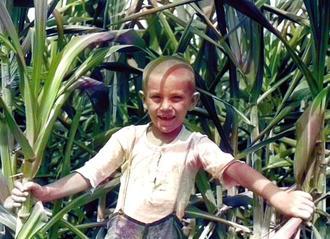 現在の沖縄市古謝のサトウキビ畑で笑顔を見せる当時7歳の故儀間政夫さん=1935年