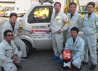 作業車には「AEDを搭載しています」が表示されている。AEDを手にする玉城さんと従業員ら=名護市