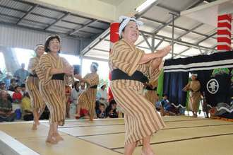 所々で立ち止まり、「ユイ」の掛け声を上げて豊年の喜びを表す「ヤマト踊り」を披露する女性=27日、多良間村仲筋の土原御願