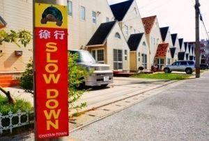 ずらりと並ぶ外国人住宅。北谷町が設置した徐行呼び掛けの看板も英語だ=同町宮城