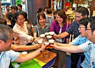 さまざまな味のビールを注文し、乾杯で盛り上がる来場者=12日午後、那覇市久茂地・タイムスビル