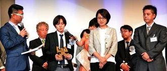 ギャラクシー賞テレビ部門の大賞に選ばれ壇上でインタビューに答えるQABの(前列左2人目から)棚原大悟さん、島袋夏子さん、新垣康之さん=2日、東京・ウェスティンホテル東京
