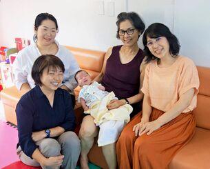 若い母親から預かった生後約1カ月の男児をあやす一般社団法人「ある」の棚原喜美枝代表理事(手前左)と安里千恵子理事(右)らスタッフ=16日、浦添市内