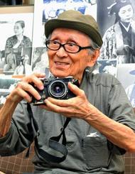 愛機のフィルムカメラを手に、思い出を語る山田實さん=2013年8月28日、那覇市久米