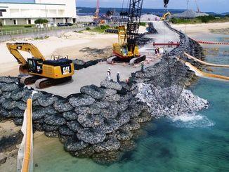 (資料写真)「N5」護岸建設予定地で海側へ投下される石材=2017年11月6日、名護市辺野古の米軍キャンプ・シュワブ(小型無人機から)