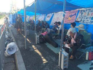 仮設テントに座り込み、歌で抗議の意志を示す市民ら=9日午前10時10分ごろ、名護市辺野古の米軍キャンプ・シュワブゲート前