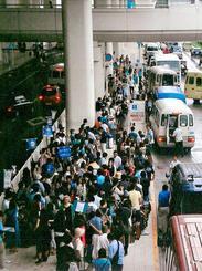 レンタカーの送迎バスを待って行列をつくる観光客ら=2015年9月7日、那覇空港国内線ビル前(県レンタカー協会提供)