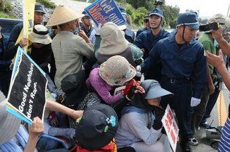 新基地建設に反対し米軍キャンプ・シュワブゲート前で抗議する市民ともみあう県警機動隊=17日午前9時55分、名護市辺野古