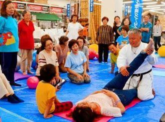 池原さんから、膝の痛みの解消法を教わる参加者=メイクマン浦添本店