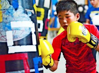 サンドバッグを打ち込む成上聖斗=中城村・琉豊ボクシングスタジオ
