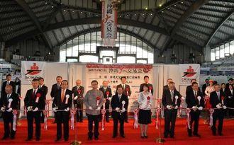 沖縄大交易会のオープニングセレモニーでテープカットをする関係者=26日午前、宜野湾コンベンションセンター展示棟
