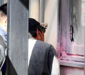 窓ガラスが割られた現場を確認する捜査員ら=22日午前9時46分、那覇市前島・自衛隊沖縄地方協力本部