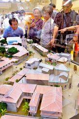 戦前に那覇市役所があった中心地(現在の東町付近)の模型に見入る来場者=20日午前、那覇市役所ロビー