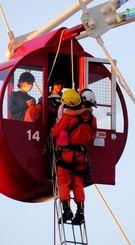閉じ込められたゴンドラから消防隊員に救助される人たち=22日午後7時6分、北谷町美浜(松田麗香撮影)