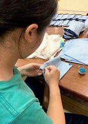 手縫いのマスクを作る女子中学生(児童自立支援施設提供)