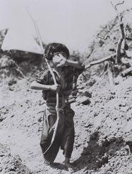 この少女は、だれに教わったのか、白旗をかざして米軍前線に近づいてきた=1945年