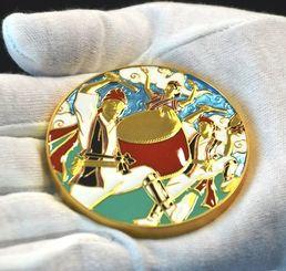 七宝を使い「エイサーまつり」をテーマにデザインされたメダル。パーランクー、三線、ハイビスカスが描かれている