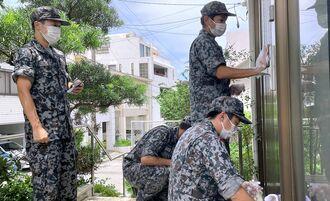 PFOSを含む泡消火剤が飛散した住宅の玄関などを洗浄する航空自衛隊員ら=26日、那覇市