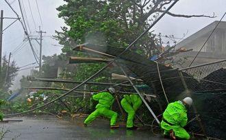 暴風で倒壊した部室のトタン屋根や柱を懸命に支える消防隊員=8日午後1時半ごろ、浦添市・仲西中学校(国吉聡志撮影)