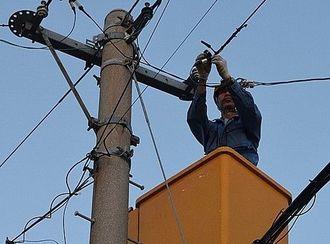 停電の復旧に向けて作業する電気工事会社の作業員=10月2日午後6時過ぎ、うるま市