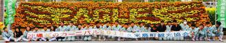 プロ野球・楽天のロゴを花で描いた久米島高校園芸科の生徒たち=29日、久米島空港