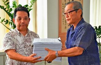平敷昭人県教育長(左)に署名を手渡した星野人史・珊瑚舎スコーレ理事長=8日、県教育庁