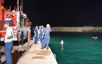 海に転落した車両を捜索する消防隊員ら=1日午後8時35分、名護漁港