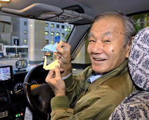 折り紙を乗客にプレゼントしている安進タクシーの與座仁志さん=10月28日、那覇市久茂地