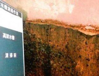 清掃前の貯水タンクの内部。壁面がさびや藻で汚れている(沖縄クリーン工業提供)