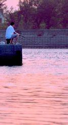 夕暮れの潮風を受けながら、釣りを楽しむ男性=22日午後7時半、南城市玉城の奥武島